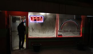 Pizza deliveryman Taras Sushko walks through the ice-crusted door of Nicco's Pizza in Coraopolis, Pa., on Monday, Jan. 6, 2014. As dangerously frigid air swept through this hard-luck Pennsylvania town on Monday night and early Tuesday morning, the few people who ventured outside needed something—mostly gambling, a drink or cigarettes. (AP Photo/Jesse Washington)