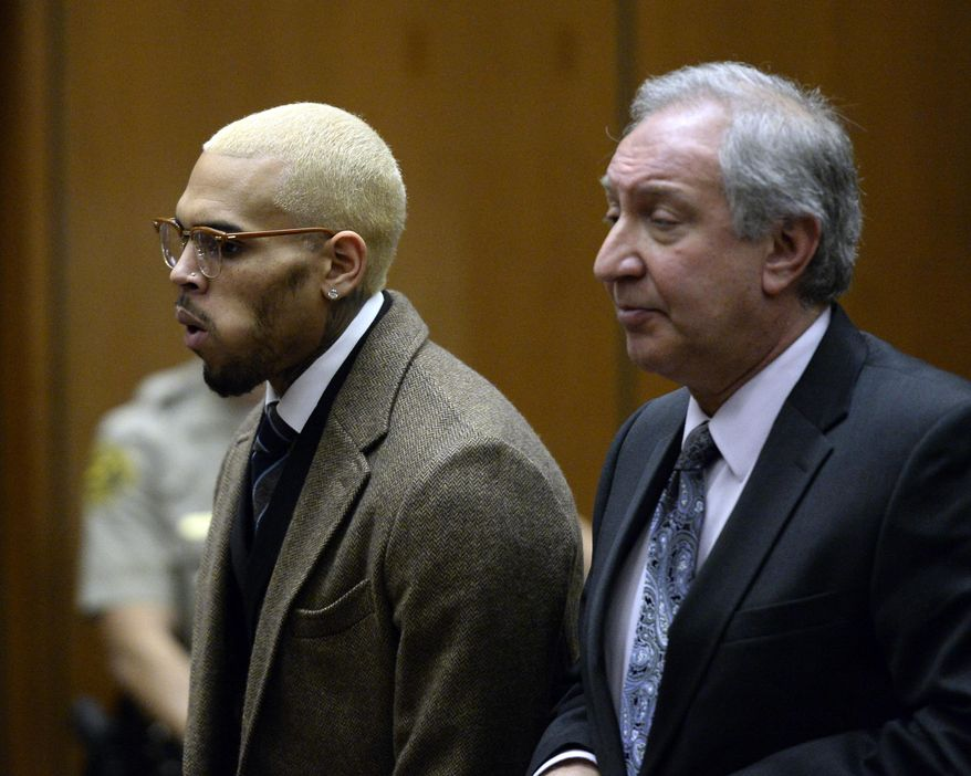 FILE - In this Dec. 16, 2013 file photo, singer Chris Brown, left, appears in court with his attorney Mark Geragos, in Los Angeles. Brown is expected to return to court for a status hearing in a case in which he's accused of hitting a man outside a Washington, D.C., hotel. The R&B singer was arrested in October after a man said the singer hit him outside the W Hotel. Brown and his bodyguard each face a misdemeanor assault charge. (AP Photo/Kevork Djansezian, Pool, File)