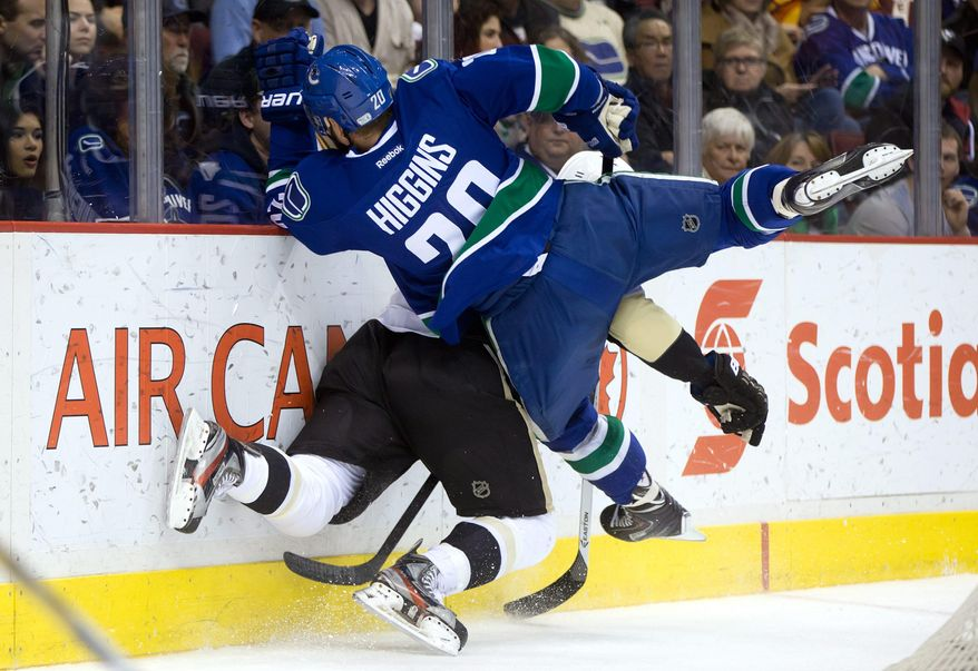 Vancouver Canucks' Chris Higgins (20)checks Pittsburgh Penguins' Joe Vitale during the first period of an NHL hockey game Tuesday, Jan. 7, 2014, in Vancouver, British Columbia. (AP Photo/The Canadian Press, Darryl Dyck)