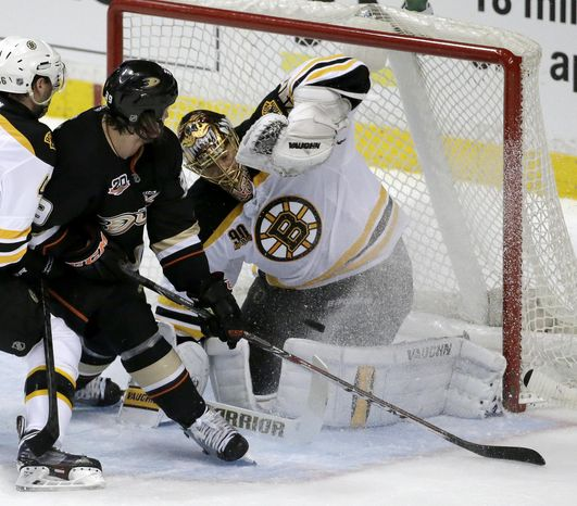 Boston Bruins goalie Tuukka Rask, right, blocks shot by Anaheim Ducks left wing Matt Beleskey during the first period of an NHL hockey game in Anaheim, Calif., Tuesday, Jan. 7, 2014. (AP Photo/Chris Carlson)