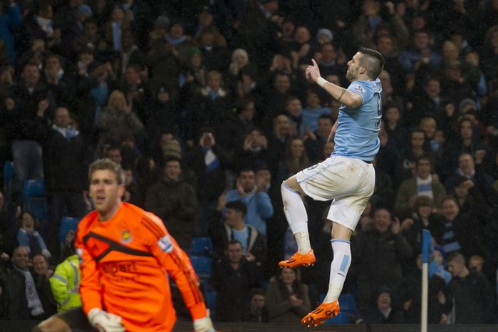 Manchester City's Alvaro Negredo celebrates after scoring his third goal past West Ham's goalkeeper Adrian, left, during their English League Cup semi-final soccer match at the Etihad Stadium, Manchester, England, Wednesday Jan. 8, 2014. (AP Photo/Jon Super)