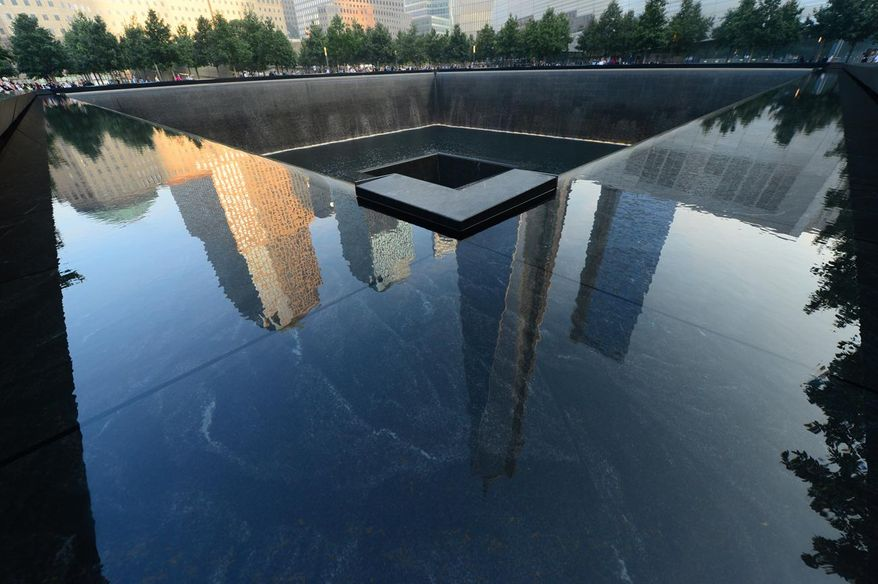 FILE - This Sept. 11, 2013 file photo shows One World Trade Center, center, is reflected on the polished wall of the September 11 Memorial on the 12th anniversary of the terrorist attacks on the World Trade Center in New York.  The 9/11 Memorial is one of a number of relatively new must-see attractions for Super Bowl fans visiting the New York City area. (AP Photo/Alejandra Villa, Pool)