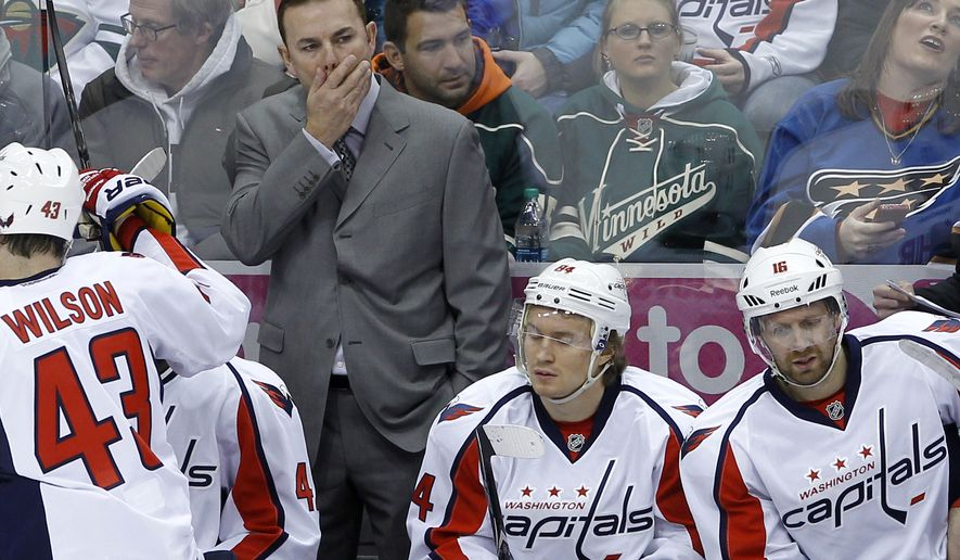 Washington Capitals head coach Adam Oates, top, watches his team from the bench during the first period of an NHL hockey game against the Minnesota Wild in St. Paul, Minn., Saturday, Jan. 4, 2014.   (AP Photo/Ann Heisenfelt)