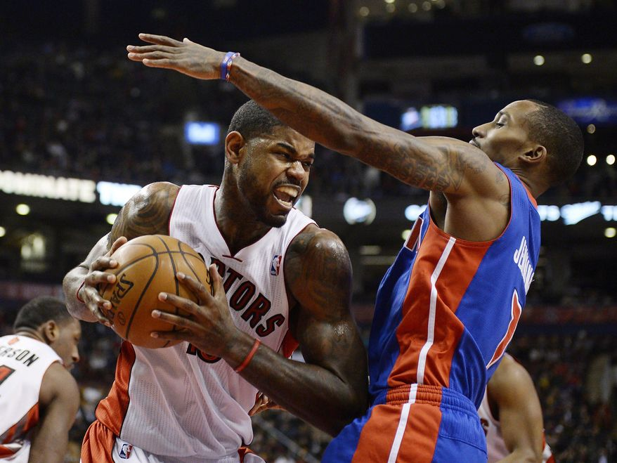Toronto Raptors forward Amir Johnson, left, drives to the net against Detroit Pistons guard Brandon Jennings during first-half NBA basketball game action in Toronto, Wednesday, Jan. 8, 2014. (AP Photo/The Canadian Press, Frank Gunn)
