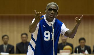 **FILE** Dennis Rodman sings Happy Birthday to North Korean leader Kim Jong Un, seated above in the stands, before an exhibition basketball game at an indoor stadium in Pyongyang, North Korea on Wednesday, Jan. 8, 2014. (AP Photo/Kim Kwang Hyon)