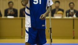 Dennis Rodman blows a kiss to North Korean leader Kim Jong Un, seated above in the stands, before an exhibition basketball game with US and North Korean players at an indoor stadium in Pyongyang, North Korea on Wednesday, Jan. 8, 2014. (AP Photo/Kim Kwang Hyon)