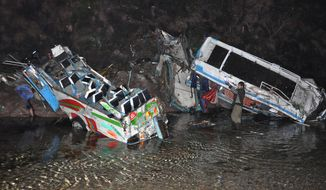 **FILE** A Pakistani volunteer looks at the wreckages of passenger buses that plunged into 50 meters ravine after colliding with each other in Salgaran near Islamabad, Pakistan, Wednesday, Jan. 8, 2014. At least 12 passengers were killed and many sustained injuries, police said. (AP Photo/B.K. Bangash)