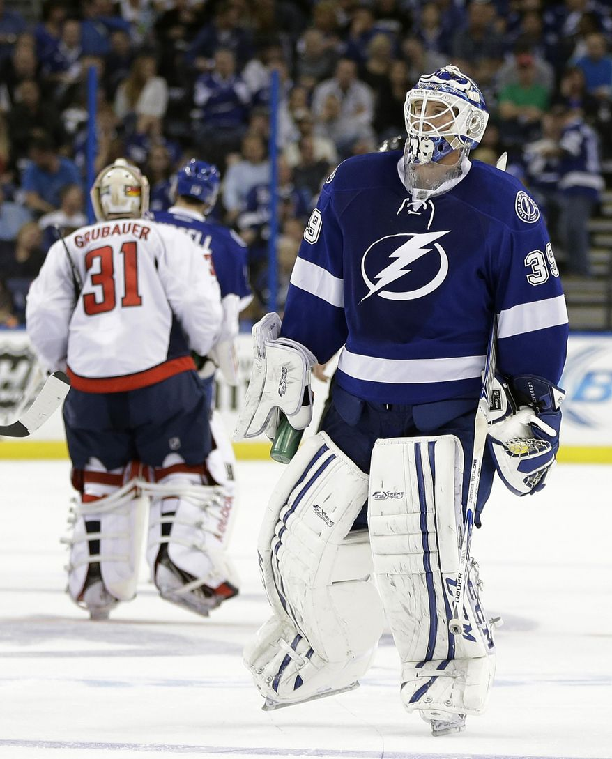 Tampa Bay Lightning goalie Anders Lindback (39), of Sweden, and Washington Capitals goalie Philipp Grubauer (31), of Germany, switch ends of the ice midway through the second period of an NHL hockey game Thursday, Jan. 9, 2014, in Tampa, Fla. The teams changed ends due to poor ice. (AP Photo/Chris O'Meara)
