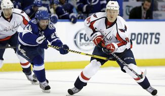 Washington Capitals center Mikhail Grabovski (84), of Germany, avoids a hook by Tampa Bay Lightning right wing Martin St. Louis (26) during the second period of an NHL hockey game Thursday, Jan. 9, 2014, in Tampa, Fla. (AP Photo/Chris O'Meara)