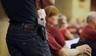 In this Aug 20, 2013, file photo, a Glock handgun is holstered on the side of Kristopher Kranz of Bloomington, Minn., as he listens to a legislative committee in St. Paul, Minn. (AP Photo/Jim Mone, File)
