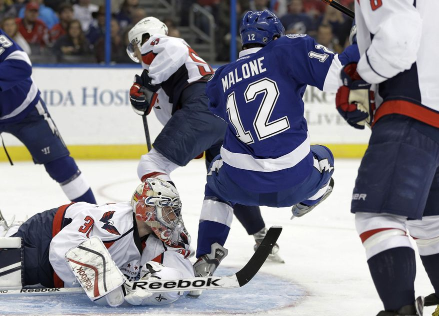 Tampa Bay Lightning left wing Ryan Malone (12) trips over Washington Capitals goalie Philipp Grubauer (31), of Germany, during the second period of an NHL hockey game Thursday, Jan. 9, 2014, in Tampa, Fla. (AP Photo/Chris O'Meara)