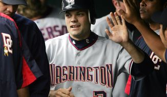 Washington Nationals' Jamey Carroll, center, is congratulated by teammates as he returns to the dugout after scoring on a double by Jose Guillen in the seventh inning of the Nationals' 9-2 victory over the Colorado Rockies in Denver on Sunday, Aug. 14, 2005. (AP Photo/David Zalubowski)