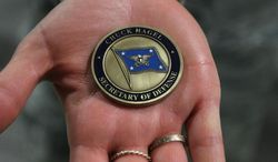 ** FILE ** Lt. Christen Ornella holds out a military coin that were handed out to airmen attending the visit of Defense Secretary Chuck Hagel on Thursday, Jan. 9, 2014 at F.E. Warren Air Force Base in Cheyenne, Wyo. It was the first time since 1982 that a defense secretary has visited the nuclear missile base. (AP Photo/Wyoming Tribune Eagle, Blaine McCartney)