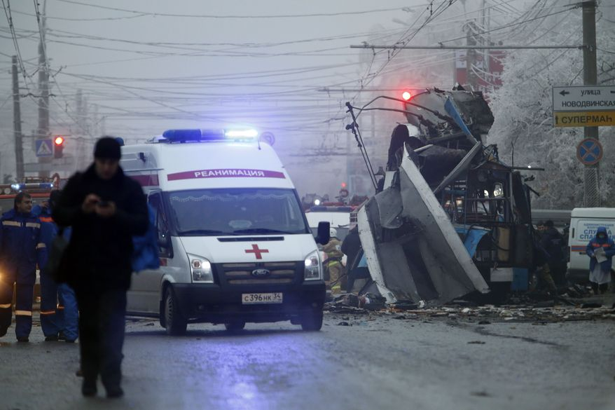 ** FILE ** In this Monday, Dec. 30, 2013, file photo, an ambulance leaves the site of an explosion after a bomb blast tore through the trolleybus, background, in the city of Volgograd. (AP Photo/Denis Tyrin, File)