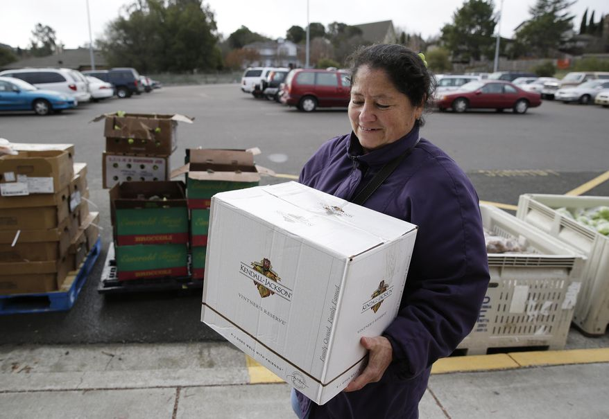 This photo taken Jan. 8, 2014 shows Maria Gonzalez carrying away her specially prepared box of food at a food bank distribution in Petaluma, Calif., part of a research project with Feeding America to try to improve the health of diabetics in food-insecure families. Doctors are warning that the federal government could be socked with a bigger health bill if Congress cuts food stamps _ maybe not immediately, they say, but if the poor wind up in doctors' offices or hospitals as a result. (AP Photo/Eric Risberg)