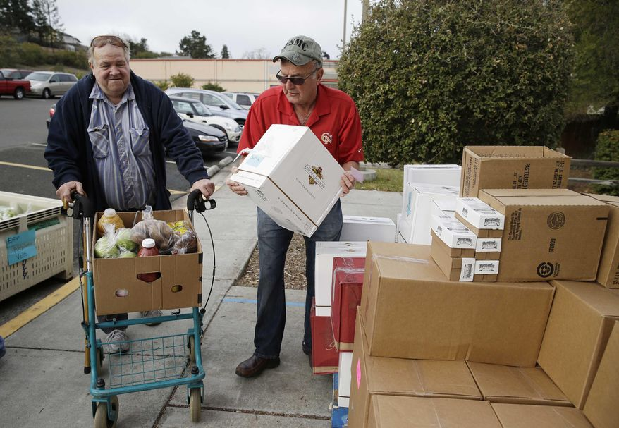 This photo taken Jan. 8, 2014 shows Steve Bosshard, right, handing over a specially prepared box of food to Gordon Hanson, left, at a food bank distribution in Petaluma, Calif., as part of a research project with Feeding America to try to improve the health of diabetics in food-insecure families. Doctors are warning that the federal government could be socked with a bigger health bill if Congress cuts food stamps _ maybe not immediately, they say, but if the poor wind up in doctors' offices or hospitals as a result. (AP Photo/Eric Risberg)