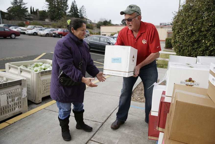 This photo taken Jan. 8, 2014 shows Steve Bosshard, right, handing over a specially prepared box of food to Maria Gonzalez, left, at a food bank distribution in Petaluma, Calif., as part of a research project with Feeding America to try to improve the health of diabetics in food-insecure families. Doctors are warning that the federal government could be socked with a bigger health bill if Congress cuts food stamps _ maybe not immediately, they say, but if the poor wind up in doctors' offices or hospitals as a result. (AP Photo/Eric Risberg)