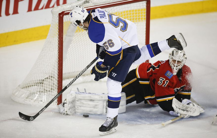 St. Louis Blues' Magnus Paajarvi, left, from Sweden, has his shot blocked by Calgary Flames goalie Karri Ramo, from Finland, during second-period NHL hockey game action against the Calgary Flames in Calgary, Alberta, Thursday, Jan. 9, 2014. (AP Photo/The Canadian Press, Jeff McIntosh)