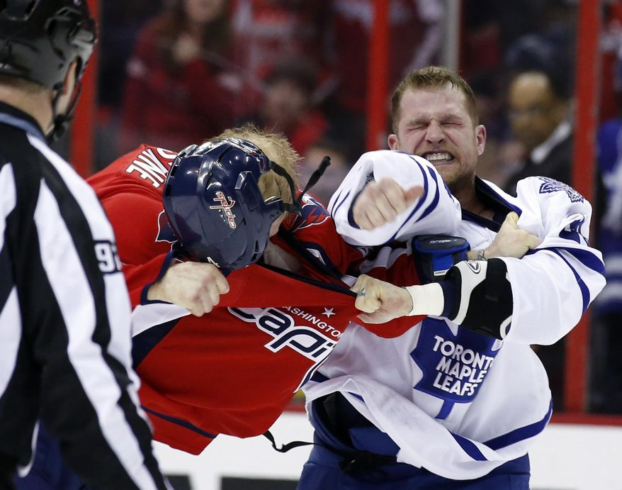 Washington Capitals defenseman John Erskine (4) loses his helmet in a fight with Toronto Maple Leafs right wing Colton Orr during the second period of an NHL hockey game, Friday, Jan. 10, 2014, in Washington. (AP Photo/Alex Brandon)