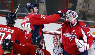 Washington Capitals defenseman Karl Alzner (27) and goalie Michal Neuvirth (30), from the Czech Republic, celebrate after an NHL hockey game against the Toronto Maple Leafs, Friday, Jan. 10, 2014, in Washington. The Capitals won 3-2. (AP Photo/Alex Brandon)
