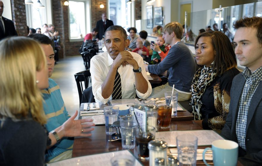 President Barack Obama listens as he has lunch with five young people at The Coupe restaurant in the Columbia Heights section of Washington, Friday, Jan. 10, 2014. The five are spearheading creative outreach efforts to connect with and help enroll young consumers through the Marketplaces or are interested in getting more involved with these efforts. Seated at the table with Obama are, from left, Anne Johnson, Andres Cruz, Obama, Jasmine Hicks, and Tommy McFly.(AP Photo/Susan Walsh)