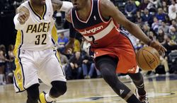 Washington Wizards guard John Wall (2) drives in front of Indiana Pacers guard C.J. Watson (32) during the first half of an NBA basketball game in Indianapolis, Friday, Jan. 10, 2014. The Pacers won 93-66. (AP Photo/AJ Mast)