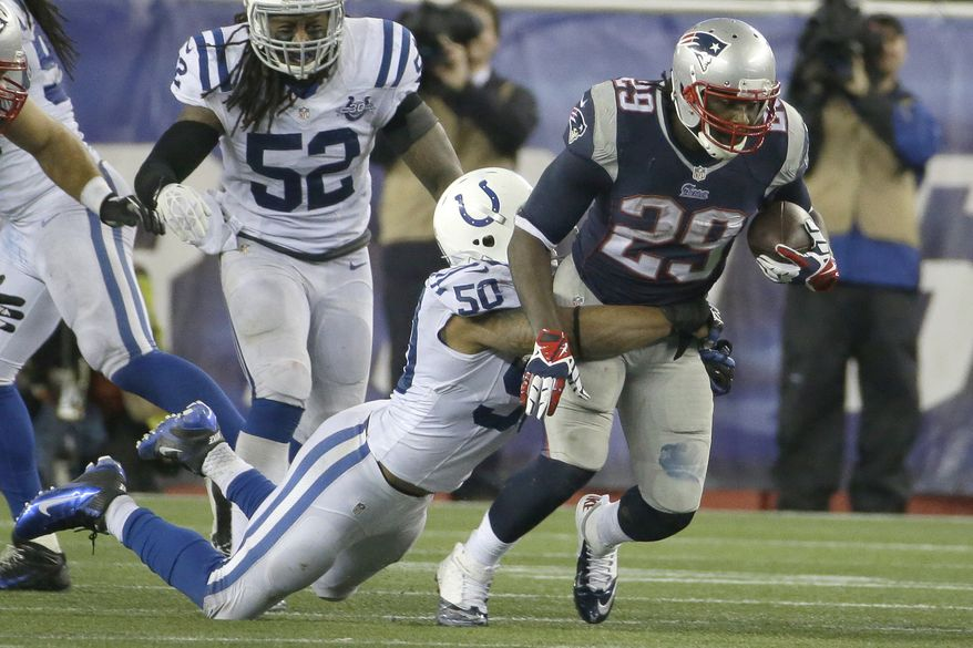 New England Patriots running back LeGarrette Blount (29) drags Indianapolis Colts linebacker Jerrell Freeman (50) with his during the second half of an AFC divisional NFL playoff football game in Foxborough, Mass., Saturday, Jan. 11, 2014. (AP Photo/Matt Slocum)