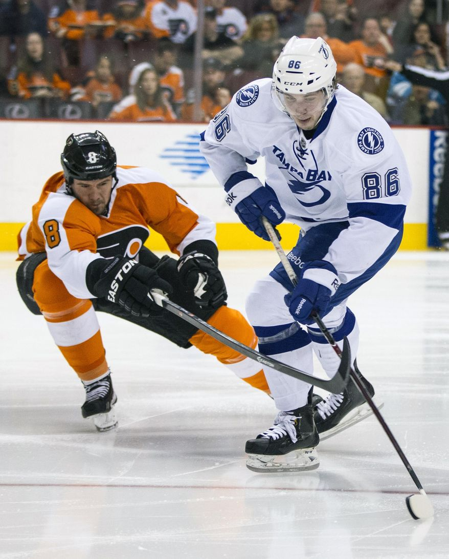 Tampa Bay Lightning's Nikita Kucherov, right, of Russia controls the puck with Philadelphia Flyers' Nicklas Grossmann, left, of Sweden, reaching for it during the first period of an NHL hockey game, Saturday, Jan. 11, 2014, in Philadelphia.  (AP Photo/Chris Szagola)