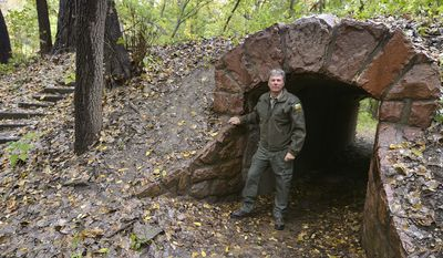 ADVANCE FOR WEEKEND EDITIONS JAN. 11-12 - In this Oct.14, 2013 photo, Ranger Kevin Pape poses near the tunnel on Tunnel Trail at Stone State Park in Sioux City, Iowa. Many of the trails at the rural Sioux City state park, including Tunnel Trail, were built by the Civilian Conservation Corps. The CCC was a New Deal program designed to promote conservation and provide employment to men out of work due to the Great Depression. (AP Photo/Sioux City Journal, Tim Hynds) MANDATORY CREDIT; MAGS OUT; NO SALES; TV OUT