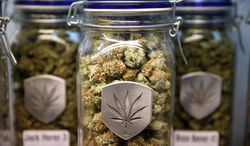 ** FILE ** Colorado officials are urging the Justice and Treasury departments to issue a guidance giving leeway to banks in states that have legalized marijuana. (associated press)