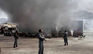 Afghan police officers watch the site of a Taliban attack last year against NATO supply trucks near the Pakistan-Afghanistan border. After more than 13 years of American bloodshed and treasure, the U.S. military will leave national security in the hands of Afghans. (Associated Press)