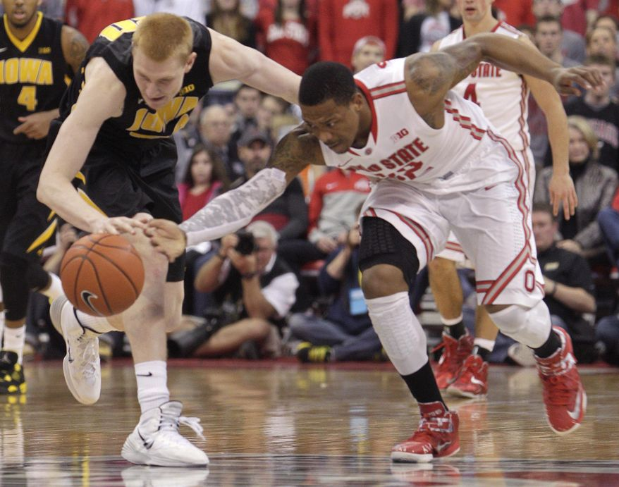 Iowa's Aaron White, left, and Ohio State's Lenzelle Smith chase a loose ball during the second half of an NCAA college basketball game on Sunday, Jan. 12, 2014, in Columbus, Ohio. Iowa won 84-74. (AP Photo/Jay LaPrete)