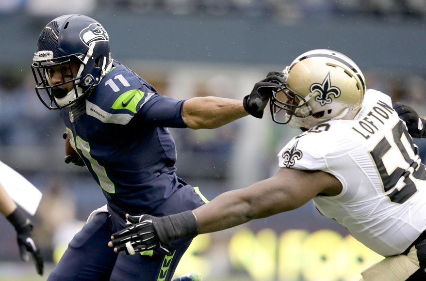 Seattle Seahawks wide receiver Percy Harvin, left, fends off New Orleans Saints middle linebacker Curtis Lofton (50) during the first half of an NFC divisional playoff NFL football game in Seattle, Saturday, Jan. 11, 2014. (AP Photo/Elaine Thompson)