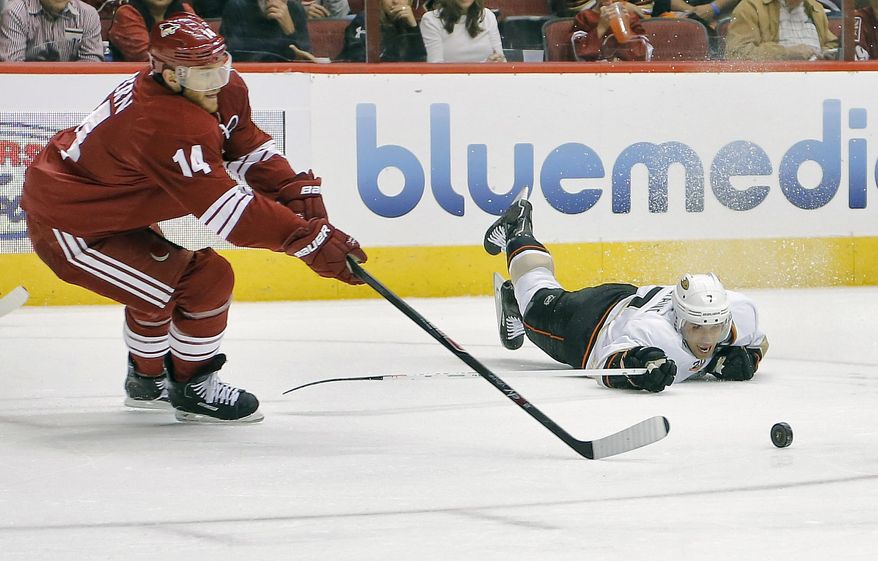 Anaheim Ducks' Andrew Cogliano (7) and Phoenix Coyotes' Jeff Halpern (14) battle for the puck during the first period of an NHL hockey game, Saturday, Jan. 11, 2014, in Glendale, Ariz. (AP Photo/Matt York)