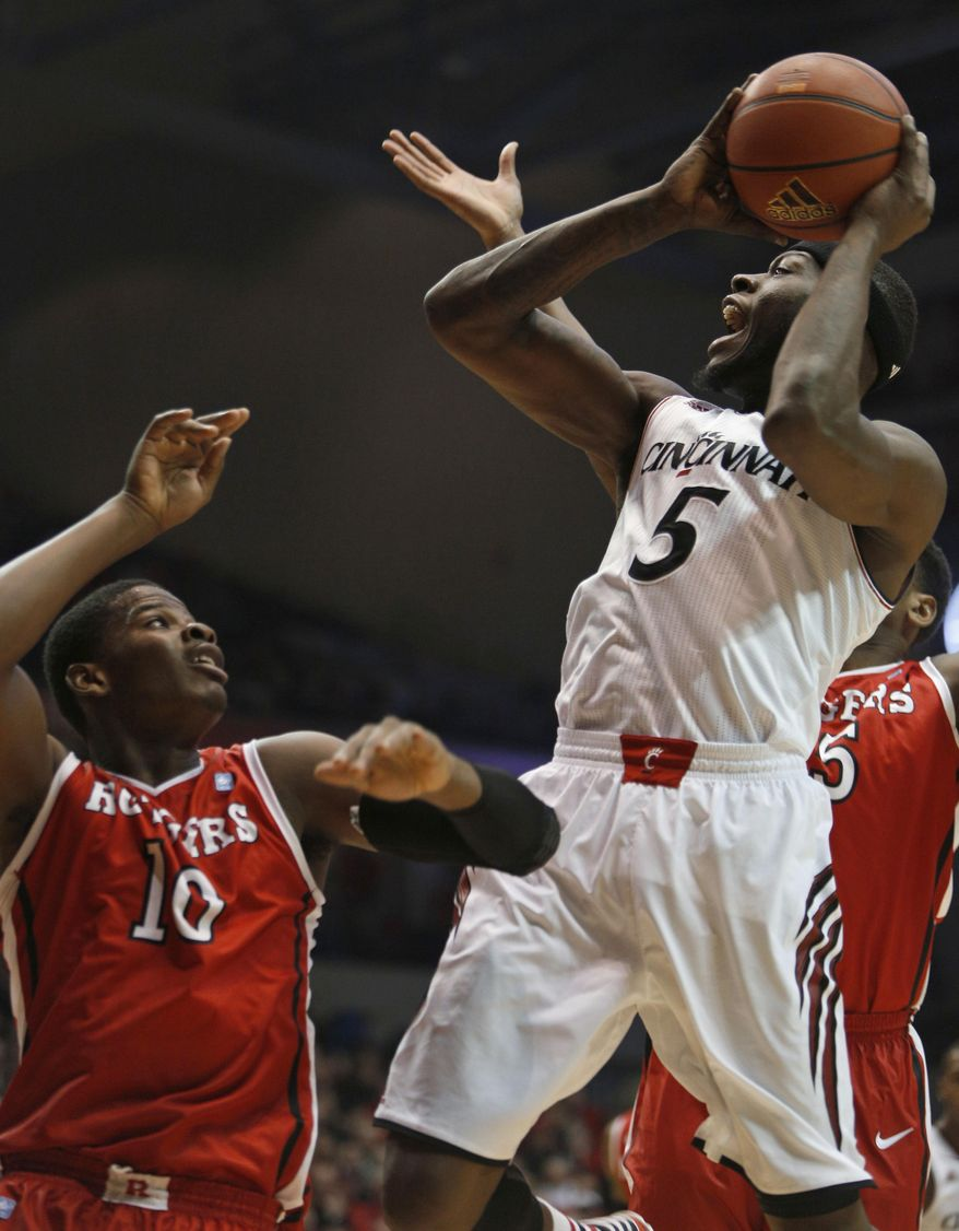 Cincinnati forward Justin Jackson (5) looks to shoot against Rutgers forward Junior Etou (10) during the first half of an NCAA college basketball game, Saturday, Jan. 11, 2014, in Cincinnati. (AP Photo/David Kohl)
