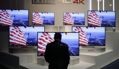 A show attendee looks at the Ultra HD 4K displays at the Toshiba booth at the International Consumer Electronics Show on Thursday, Jan. 9, 2014, in Las Vegas. (AP Photo/Jae C. Hong)