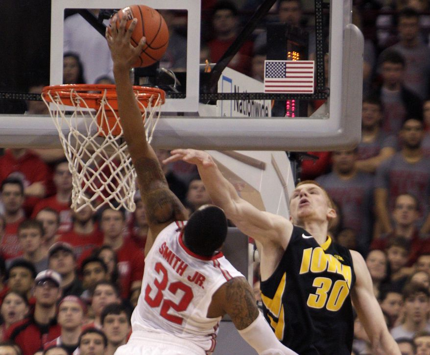 Ohio State's Lenzelle Smith, left, tries to dunk the ball over Iowa's Aaron White during the first half of an NCAA college basketball game on Sunday, Jan. 12, 2014, in Columbus, Ohio. (AP Photo/Jay LaPrete)