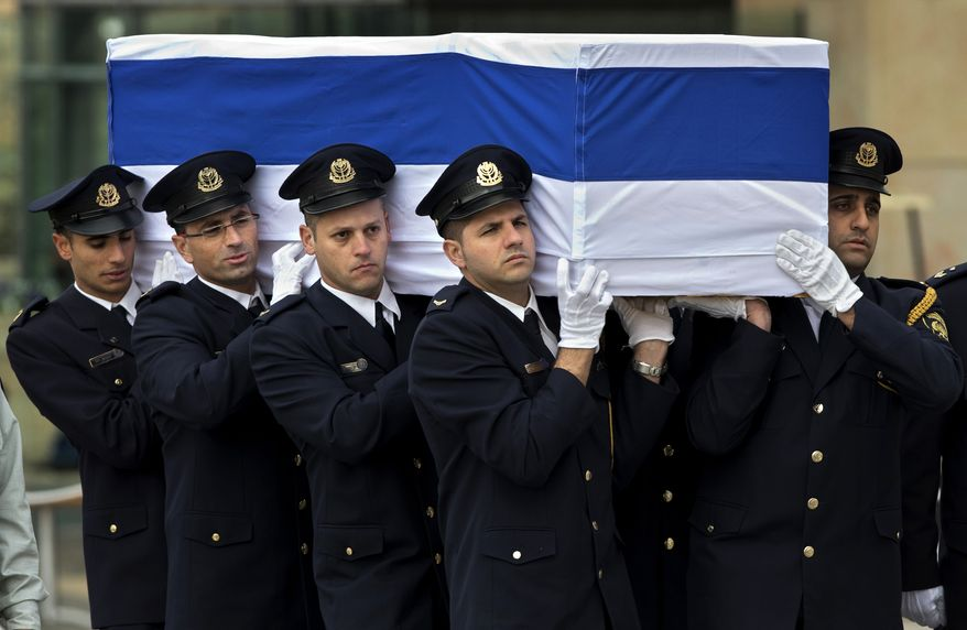 Members of the Knesset guard carry the coffin of late Israeli Prime Minister Ariel Sharon at the Knesset, Israeli Parliament, in Jerusalem, Sunday, Jan. 12, 2014. Sharon, the hard-charging Israeli general and prime minister who was admired and hated for his battlefield exploits and ambitions to reshape the Middle East, died Saturday, eight years after a stroke left him in a coma from which he never awoke. He was 85. (AP Photo/Bernat Armangue)