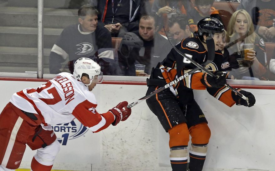 Detroit Red Wings right winger Mikael Samuelsson (37), of Sweden, and Anaheim Ducks defenseman Ben Lovejoy (6) tangle in the first period of an NHL hockey game in Anaheim, Calif., Sunday, Jan. 12, 2014.  (AP Photo/Reed Saxon)