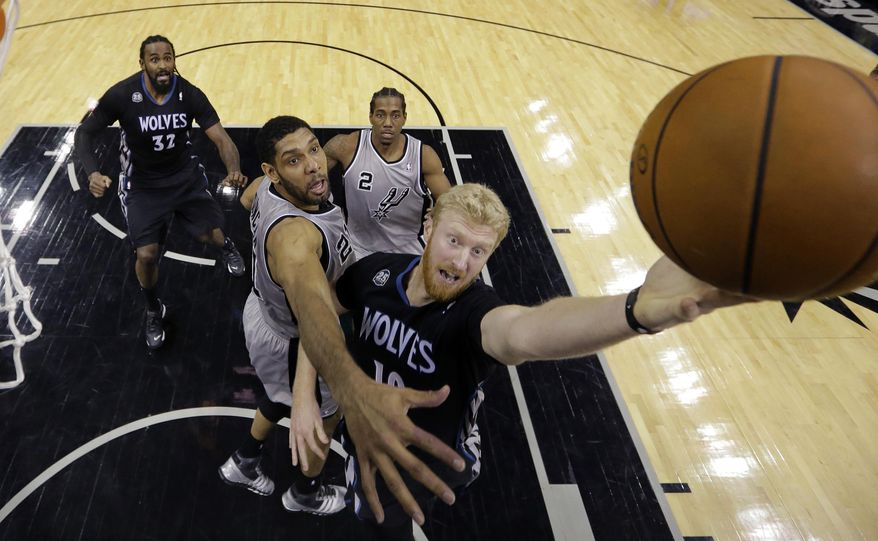 Minnesota Timberwolves' Chase Budinger, right, drives past San Antonio Spurs' Tim Duncan, center, to score during the first half of an NBA basketball game on Sunday, Jan. 12, 2014, in San Antonio. (AP Photo/Eric Gay)