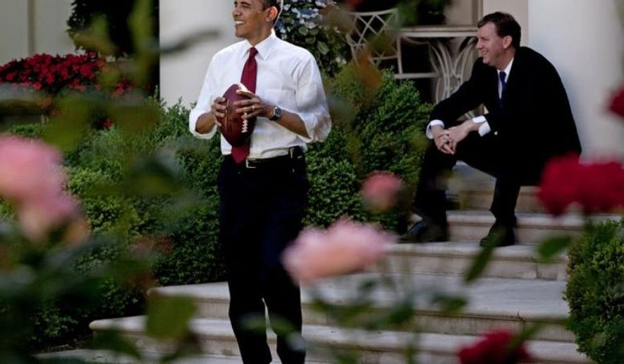 President Barack Obama throws a football to a staff member in the Rose Garden, while White House Trip Director Marvin Nicholson watches, May 22, 2009. (Official White House Photo by Pete Souza)