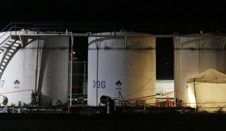 Workers at Freedom Industries continue through the night to empty storage tanks of chemicals at it's plant in Charleston, Va., Sunday, Jan. 12, 2014.  A chemical spill at the company has deprived 300,000 West Virginians of clean tap water for four days.(AP Photo/Steve Helber)