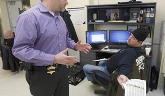 In this Jan. 8, 2014 photo, John Blair, left, executive director of the Cook County Sheriff's Office Intelligence Center, consults with Officer John Slepski about a firearms background check Slepski is performing at the center in Chicago. Requests to carry a gun in public are pouring in at more than 1,000 per day in the nation's last state to allow the practice, triggering concerns among Illinois' local law enforcement authorities that they could fall behind in a special 30-day process to weed out applicants with a history of violence. The Cook County Sheriff's office says it already has found about 100 applications it plans to contest after the law went into effect Jan. 5. (AP Photo/Charles Rex Arbogast)