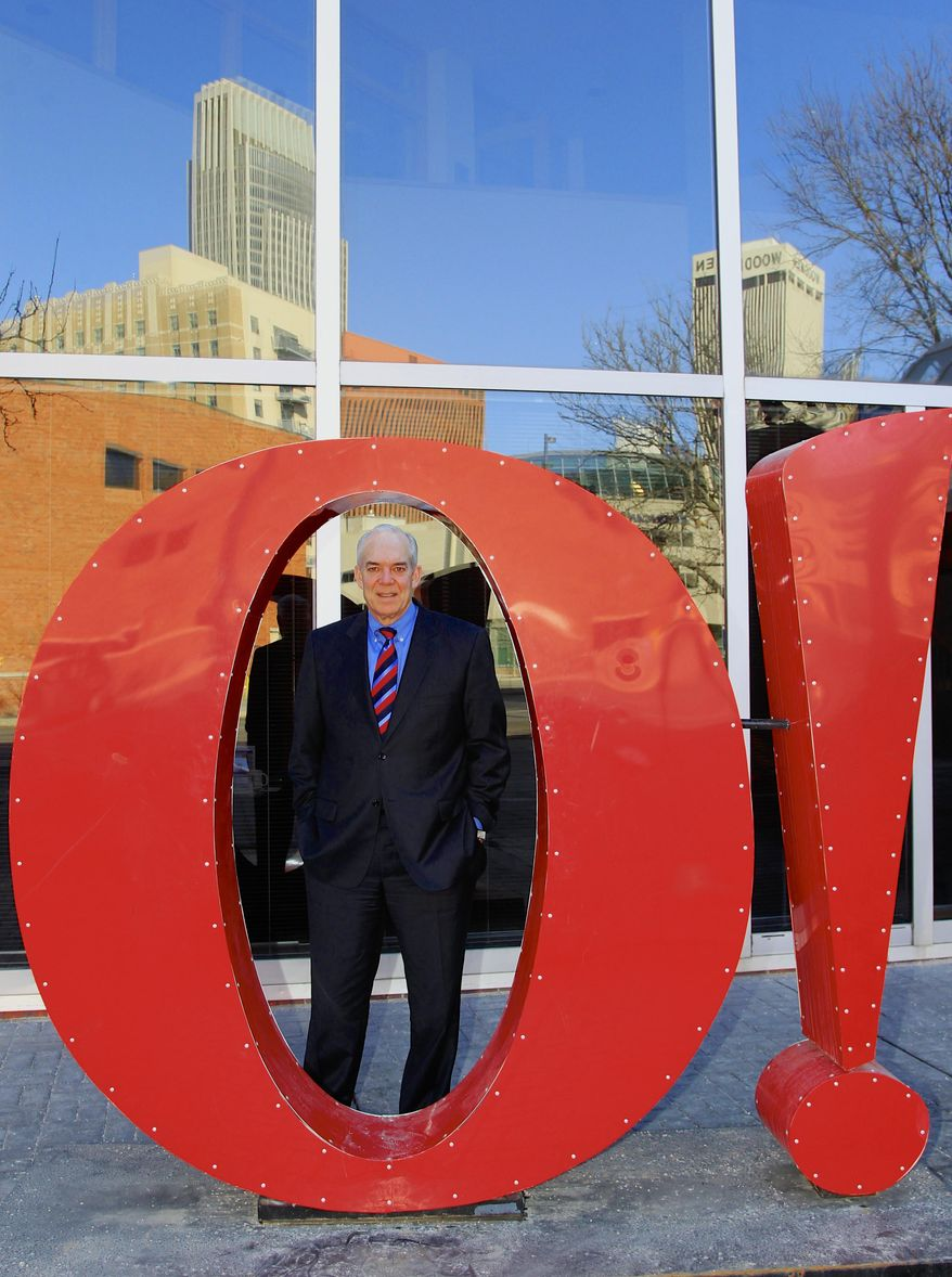 """Greater Omaha Chamber of Commerce president and CEO David Brown poses for a photo behind the """"Big O"""" sculpture and the Omaha skyline, in Omaha, Neb., Monday, Jan. 13, 2014. Folks who watched the Denver Broncos' NFL playoff win over the San Diego Chargers on television Sunday couldn't help but notice how often, and loudly, Payton Manning used the code word """"Omaha"""" as he barked signals. Brown said he wants to explore the possibility of hiring Manning, one of the sporting world's top pitchmen, to shoot a promotional ad for Omaha. (AP Photo/Nati Harnik)"""