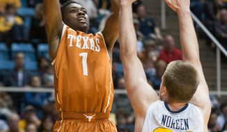 Texas' Isaiah Taylor, left, looks to shoot over West Virginia's Kevin Noreen during the first half of an NCAA college basketball game, Monday, Jan. 13, 2014, in Morgantown, W.Va. (AP Photo/Andrew Ferguson)