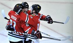 Chicago Blackhawks' Jonathan Toews (19), celebrates with teammates Patrick Sharp (10), and Marian Hossa (81), after scoring a goal during the second period of an NHL hockey game against the Edmonton Oilers in Chicago, Sunday, Jan., 12, 2014. (AP Photo/Paul Beaty)