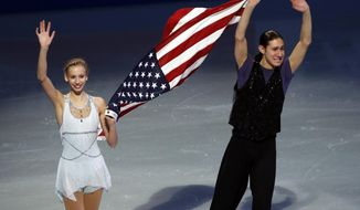 U.S. Olympic figure skaters Polina Edmunds and Jason Brown carry a flag and wave to the crowd at the end of their skating spectacular after the U.S. Figure Skating Championships in Boston, Sunday, Jan. 12, 2014. (AP Photo/Elise Amendola)