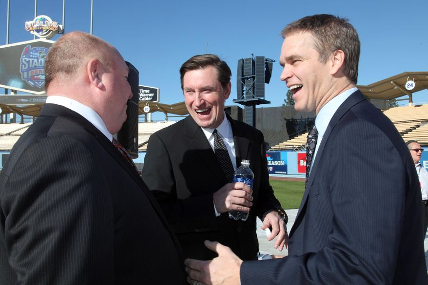 Head Coach of the Anaheim Ducks, Bruce Boudreau, left, former NHL players, Wayne Gretzky, center, and Luc Robitaille, President of business operations for the Los Angeles Kings of the National Hockey League talk about the Dodger Stadium's upcoming 2014 NHL Stadium Series hockey game in Los Angeles, on Monday, Jan. 13, 2014. An ice skating rink is being built for the 2014 NHL Stadium Series Los Angeles game between the Kings and Ducks at Dodger Stadium on Jan. 25. (AP Photo/Nick Ut)