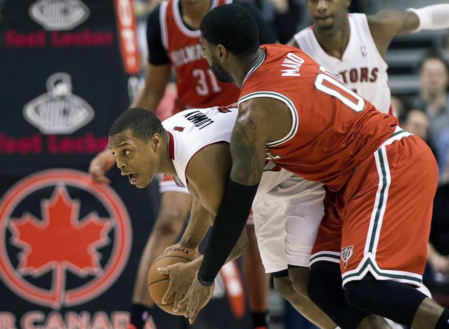 Toronto Raptors guard Kyle Lowry, left, battles for the ball against Milwaukee Bucks guard O.J. Mayo during first half NBA basketball game in Toronto, Monday, Jan. 13, 2014.  (AP Photo/The Canadian Press, Nathan Denette)