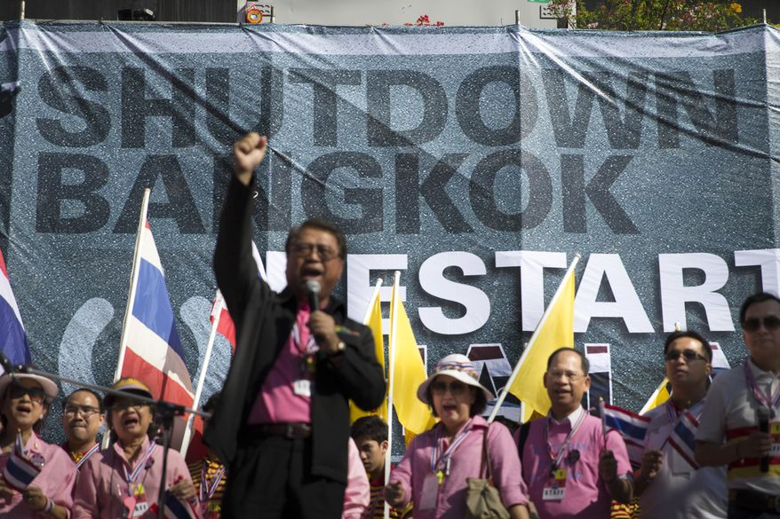 "A speaker rallies anti-government protestors with a banner reading: ""Shutdown Bangkok"" outside the MBK Center shopping mall in the Pathumwan district, Sunday, Jan. 12, 2014, in Bangkok, Thailand. Anti-government protesters took over key intersections in Thailand's capital Monday, halting much of the traffic into Bangkok's central business district as part of a months-long campaign to thwart elections and overthrow the democratically elected prime minister. (AP Photo/John Minchillo)"